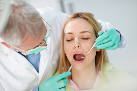 fix jaw: Close up photo to female patient on teeth review in dental practice Stock Photo