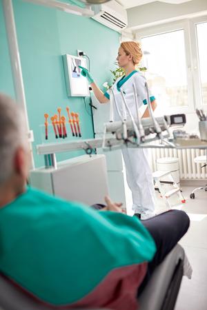 Female dentist examining dental X-ray in dental clinic