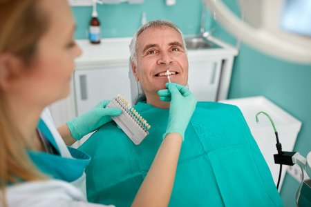 Senior man in dental chair with female dentist compare dental color for dentures Stock Photo
