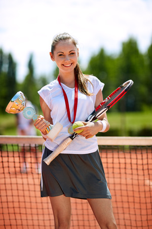 successes: Female winner in tennis with winning cup and medal on court