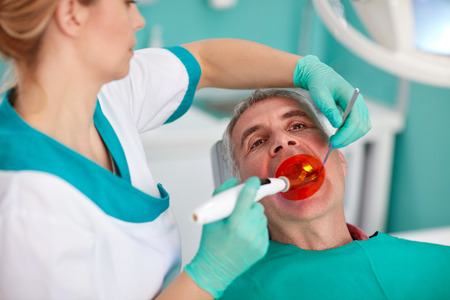 Female dentist with special lighting instrument repairing tooth to patient at clinic Stock Photo
