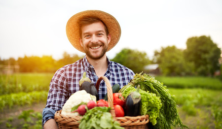 Cheerful farmer with organic vegetables in garden Imagens