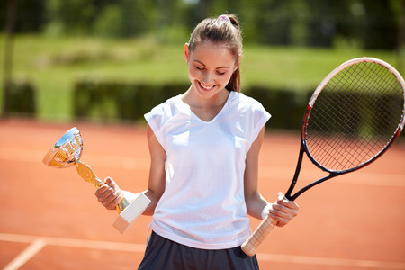 successes: Shy young girl with goblet on tennis court