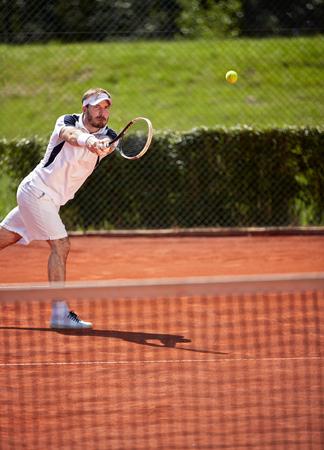 vigorously: Sportsman vigorously playing tennis in tennis court Stock Photo