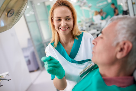 Female dentist shows to male patient closest color of teeth for dentures