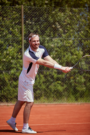 Man with racket on tennis court playing tennis, lower body part