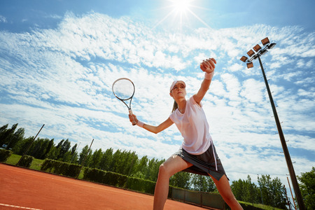 Female tennis player at training on bright day