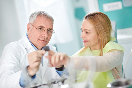 Nice young woman in dental chair and dentist talk about her snapshot on dental clinic