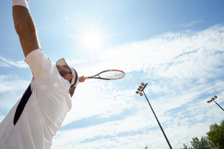 shinning: Tennis player serving ball on tennis court on shinny day