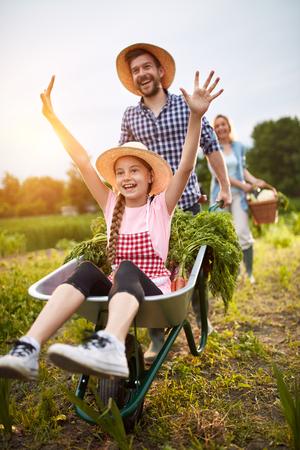 granja: niña encantada que se divierte con el granjero masculino en jardín de vehículos