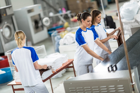 dry cleaner: Back view worker agrees ironed textile in dry cleaner Stock Photo