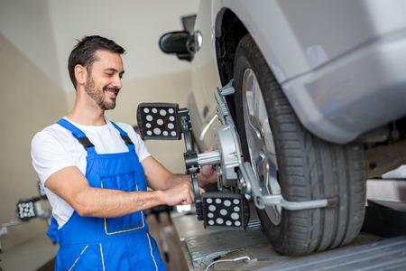 aligning: auto mechanic at wheel alignment work with sensor