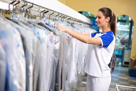 dry cleaner: Female employees checks clothes in plastic bags