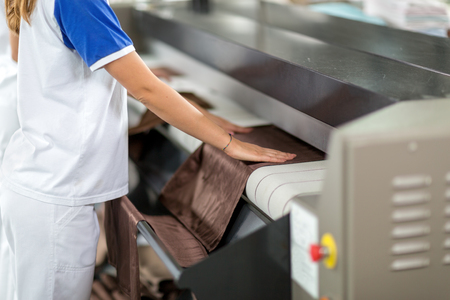 dry cleaner: Woman ironing of machines in dry cleaner Stock Photo