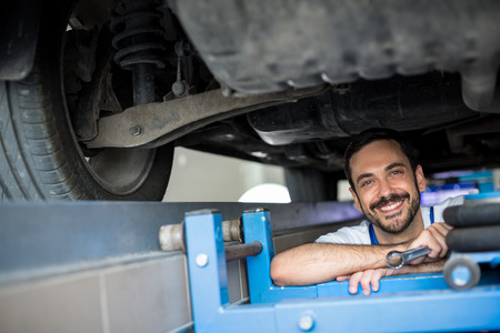 underneath: male mechanic working under car smiling