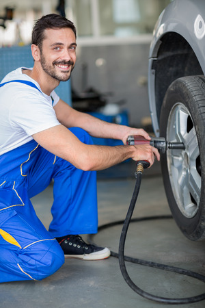smiling mechanic changing tyre on car wit hydraulic wrench Stock Photo