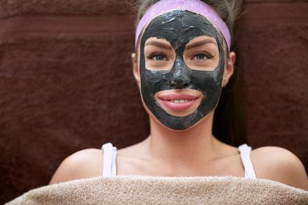Mujer bonita con la máscara cosmética negro en la cara, el concepto - belleza, cuidado de la salud. Foto de archivo