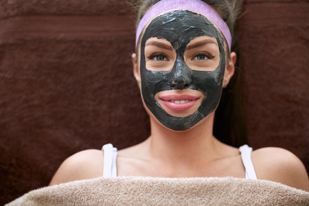 black mask: Pretty woman with cosmetic black mask on face, concept - beauty, healthcare.