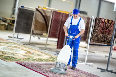 Werknemer reiniging stofzuiger tapijten Stockfoto