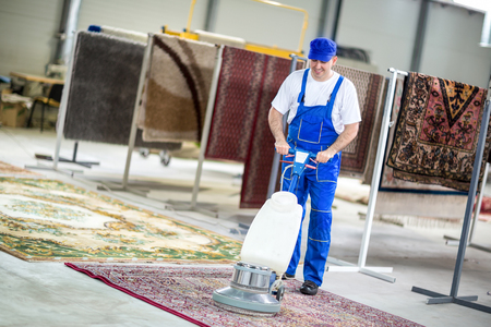 Worker cleaning vacuum cleaner  carpets Imagens