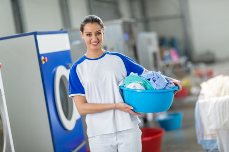 dry cleaners: Smiling woman holding laundry basket with clean clothes Stock Photo