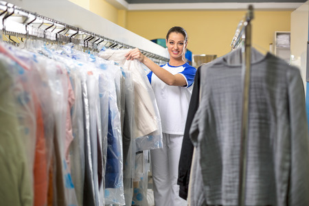dry cleaner: Smiling woman hanging clothes in plastic bags Stock Photo