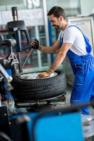 wheel balancing: mechanic repairman balancing  car wheel on balancer