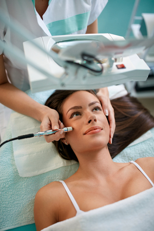 beautiful woman receiving cosmetic treatment of wrinkles prevention, microdermabrasion Stock Photo