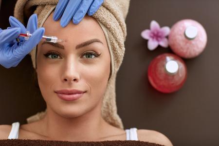 Mujer de la belleza la aplicación de inyecciones de botox. botox, tratamientos cosméticos, eliminación de arrugas, las inyecciones de Botox