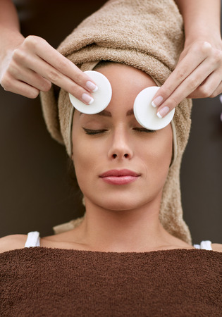 eye pad: Skin care - woman cleaning face by beautician