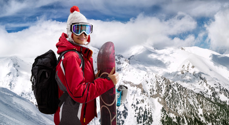 beautiful young woman smiling and holding a snowboard standing on top of mountain