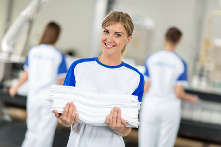 dry cleaner: Smiling employed holding clean and ironing textiles in chemical cleaners