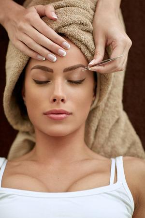 Jonge vrouwen met behandeling epileren wenkbrauwen bij schoonheidssalon Stockfoto