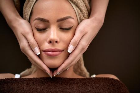 regeneration: Beautiful young woman enjoying during facial massage in cosmetic salon close up Stock Photo