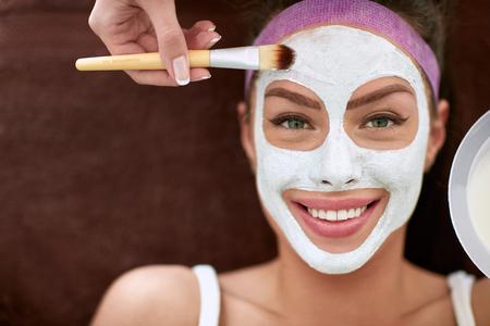 pulizia viso: Bella ragazza sorridente con la mascherina cosmetica sul trattamento spa per la pelle del viso