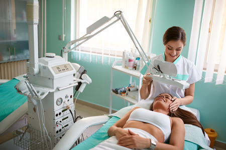 Cheerful young girl is getting facial treatment by beautician at spa clinic