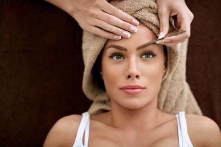 Beautiful woman receiving professional eyebrow shaping