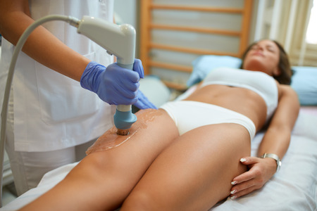 shockwave: attractive woman in beauty salon on localized anti fat treatment therapy on the thigh
