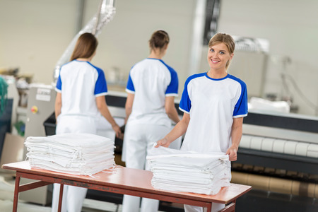 dry cleaners: Women employed agree ironing textiles in chemical cleaners Stock Photo