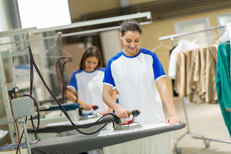 dry cleaners: Smiling women iron textile on ironing board Stock Photo