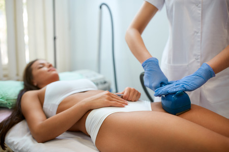 Young woman making a figure correction with professional device at spa clinic, deep oscillation causes the training of muscles is achieved by tightening the same