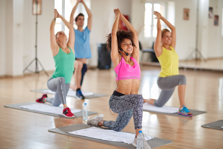 Yoga exercises with curly female instructor with hands up clasped above head in gym