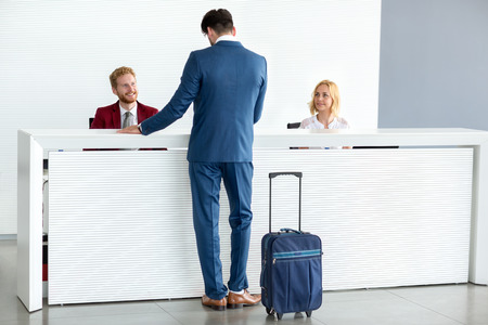 check in: Kind female receptionist wish welcome to guest Stock Photo
