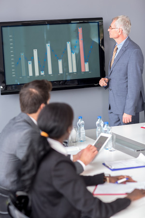 presenting: Senior manager presenting chart at meeting office