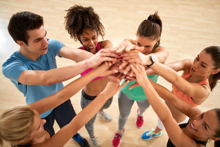 pep: Group of fitness exercisers with hands over each other in gym