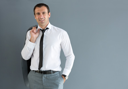 over the shoulder: Nonchalant male model posing with jacket over shoulder Stock Photo
