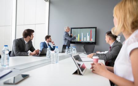 company director: Director of company present business plan while employees listen Stock Photo