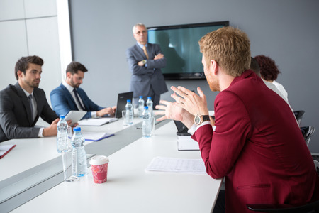 employ: Male employ present his opinions to director and collogues in meeting room