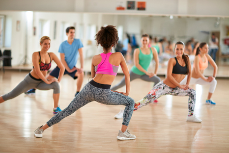 Young female instructor show exercises to fitness group at gym