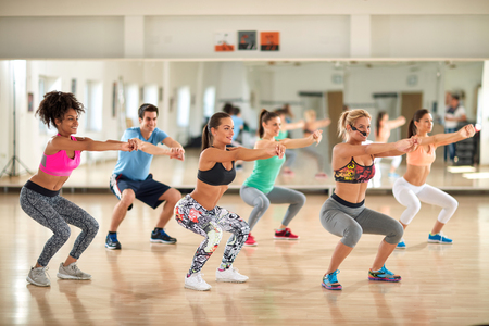 grupo de hombres: instructor de sexo femenino bastante con los jóvenes haciendo ejercicios en el gimnasio Foto de archivo